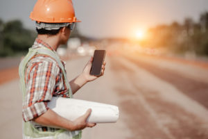 An engineer checking his smartphone at jobsite, if injured on the job speak to a skilled Yorktown Workers' Comp Lawyer.