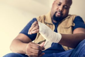A man in a construction worker clothing putting a bandage on his hand, representing how one can benefit from calling a Newport News workers' compensation attorney.