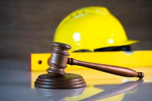 A gavel with a construction hat in the background, representing how our Smithfield workers' compensation attorneys can represent you.