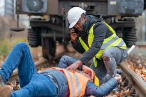 A man calling for help while another lies on railroad tracks representing how you should call a Hampton railroad injury attorney today.